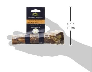 Half a deer shank bone held up by an outline of a hand to give a reference of its size. Produced by Ziwipeak for dogs' oral health