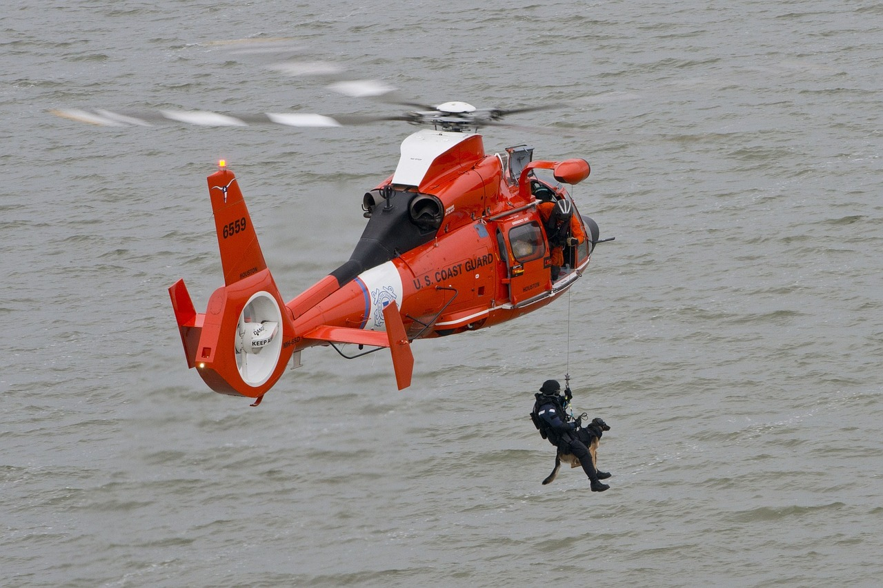 US Coast Guard Helicopter with a man suspended saving a dog