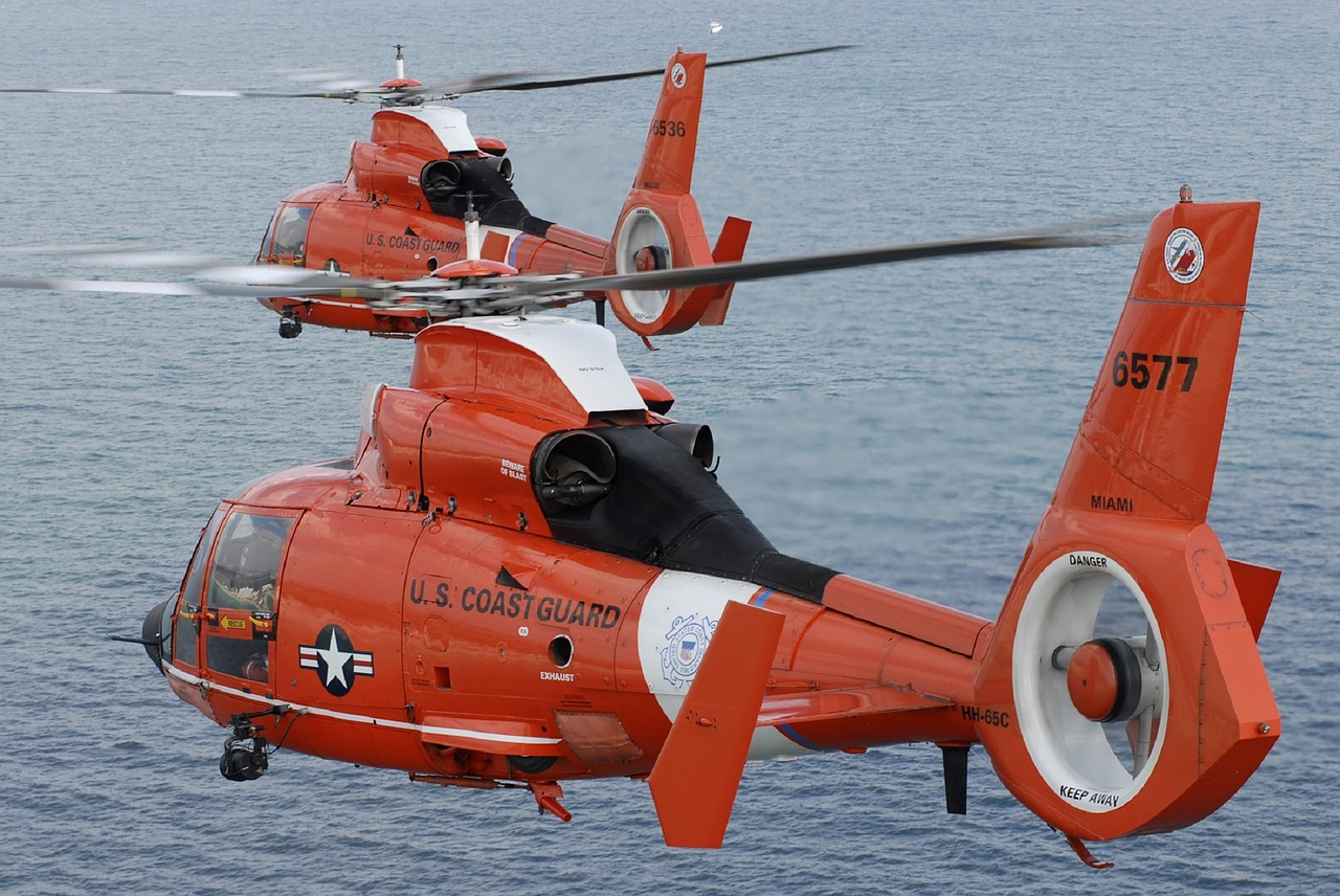 Two US Coast Guard helicopters flying over the ocean