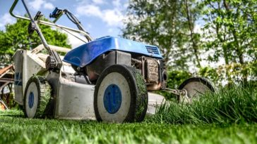 A Lawnmower on a lawn mowing grass on someones yard