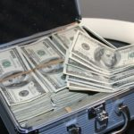 A suitcase full of 100 dollar bills. Currency from the United States. Article about how to save or finance for the holidays and black Friday shopping.