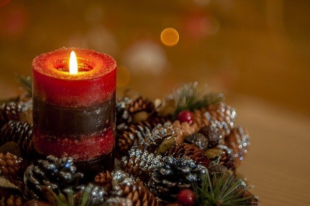 Photo of a candle with Christmas decorations. Article about actives to do if you are alone on Christmas